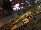 60 ton daikin air conditioning unit suspended by yellow truck with crane on city street